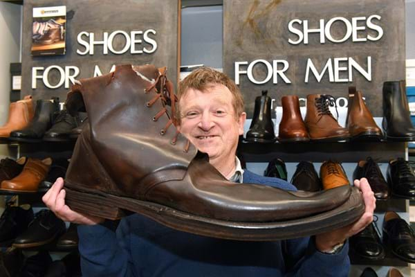 David Gummers with a giant brown boot - one of two - being auctioned by 1818 Auctioneers on Tues 6 August..jpg