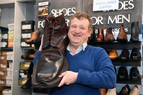 David Gummers with a giant brown boot, one of two, being auctioned by 1818 Auctioneers on Tues 6 August..jpg